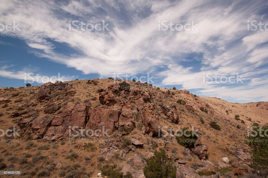 High deset rocky hillside with blue sky and beautiful couds stock photo