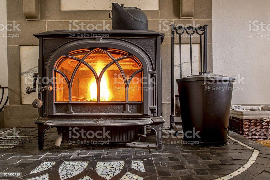 High efficiency cast iron wood stove burning firewood stock photo