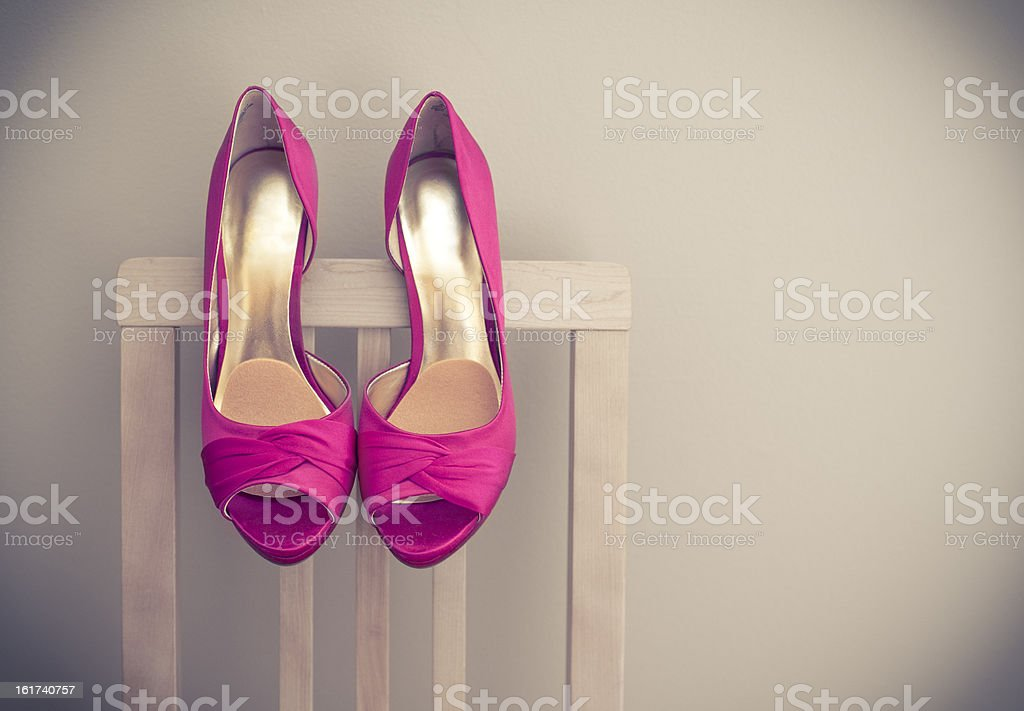 High Heel Shoes Hanging off Chair stock photo