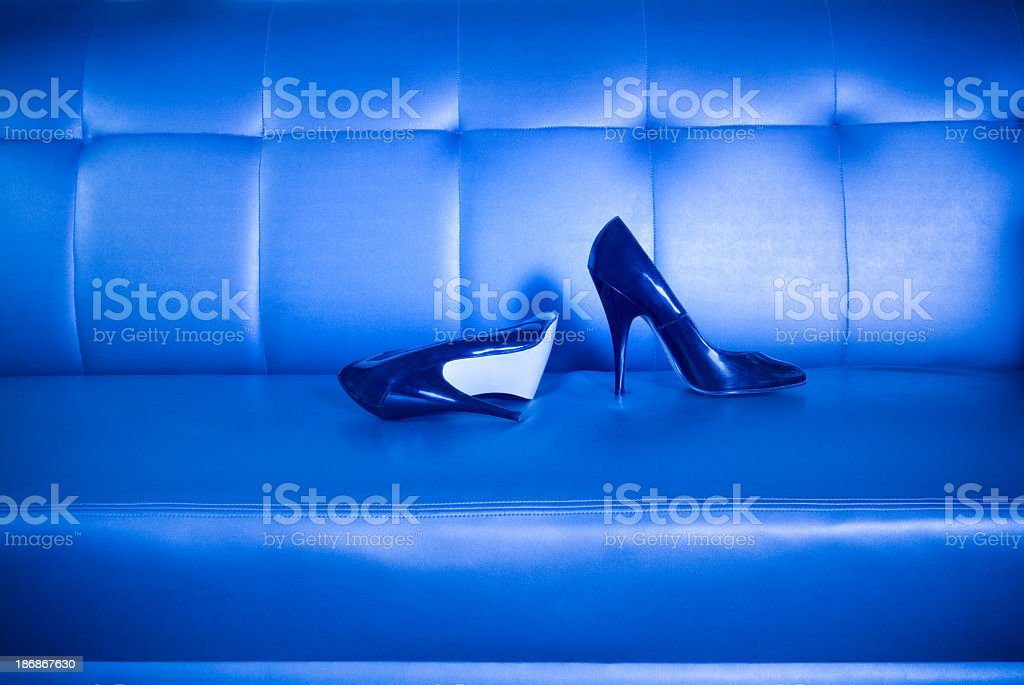 High Heel Shoes Lying on a Sleek Leather Couch stock photo