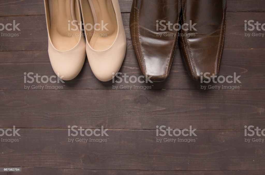 High heels and leather shoes are on wooden background stock photo