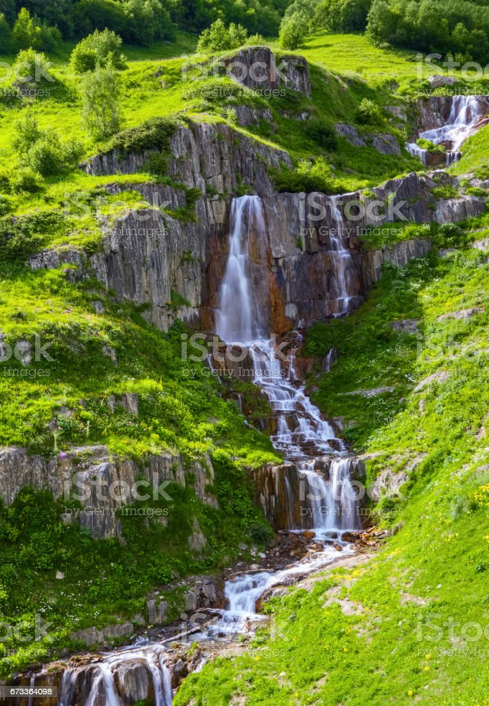 High in the mountains, among the green meadows and rocks flows extremely beautiful rapid waterfall. Upper Svaneti, Georgia, Europe. stock photo