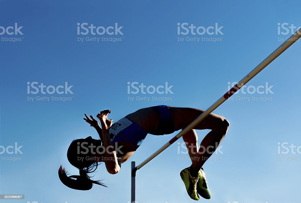 High jump silhouette against the blue sky stock photo