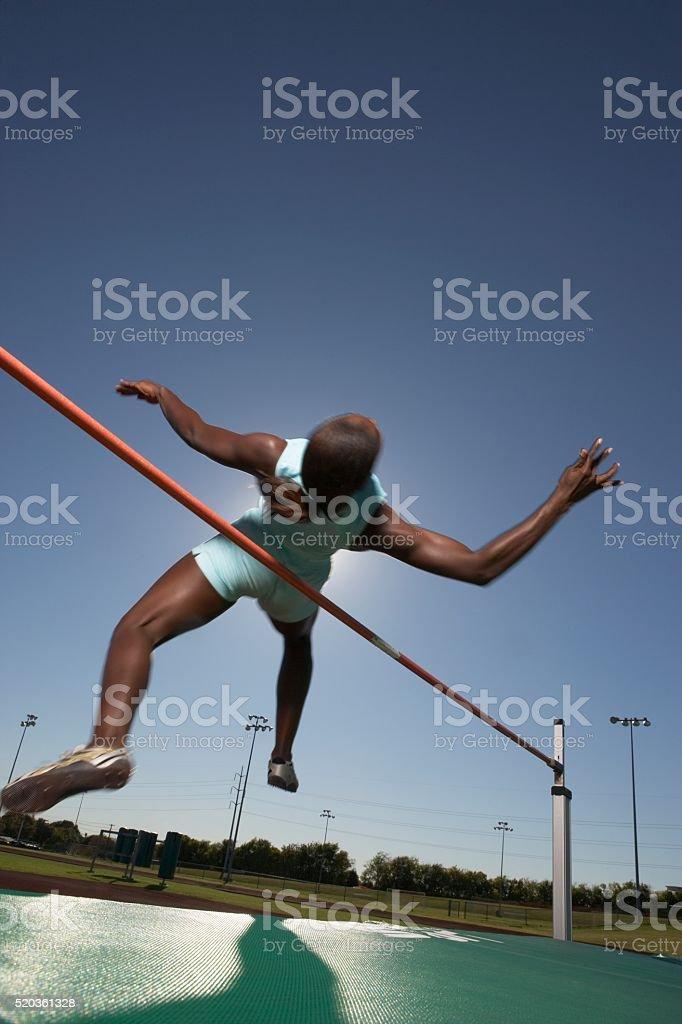 High jumper clearing bar stock photo