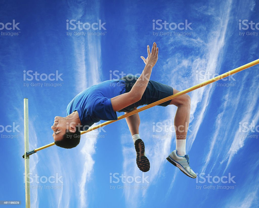 High Jumper Over Hurdle Against Sky stock photo