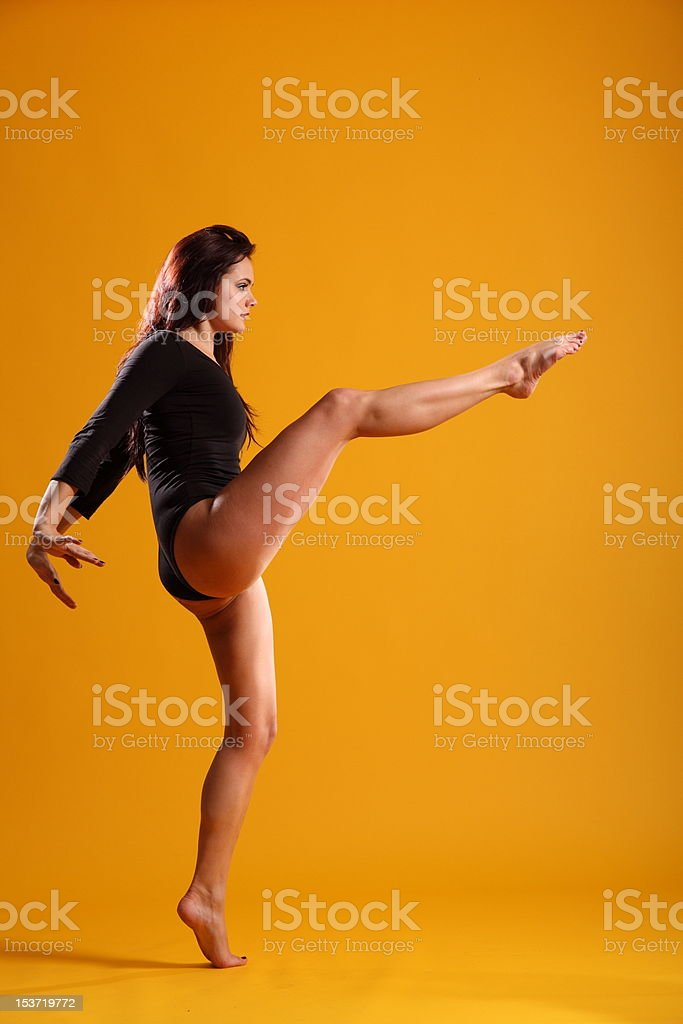 High kick dance move by beautiful woman in profile royalty-free stock photo