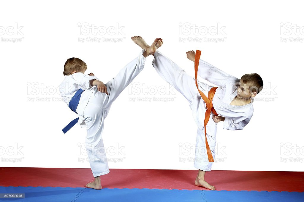 High kicks legs two athletes are training on the mat stock photo
