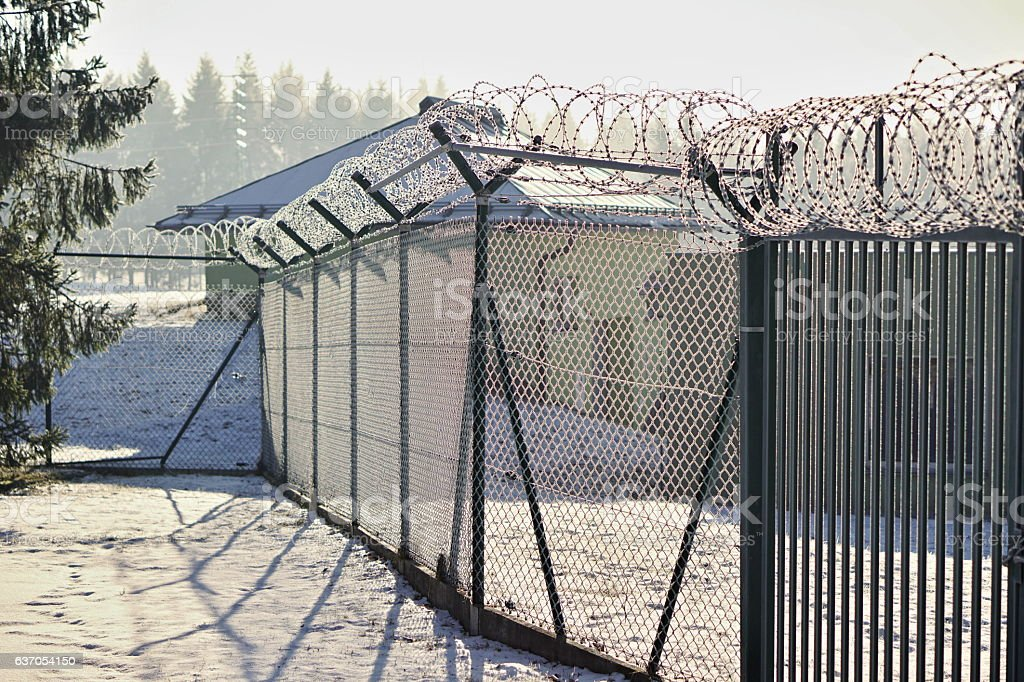 High metal fence with sharp barbed wire on the top stock photo