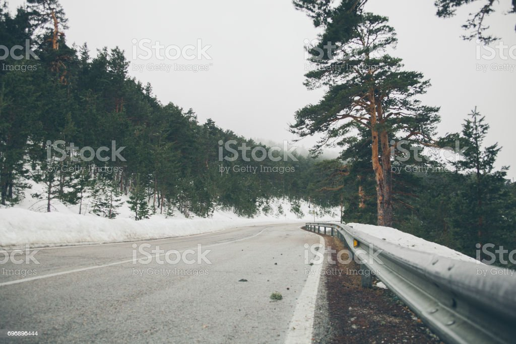 High mountain road. Mountain road landscape covered with snow.  Beautiful view of mountain road in the forest covered with snow. Mountains of Navacerrada. stock photo