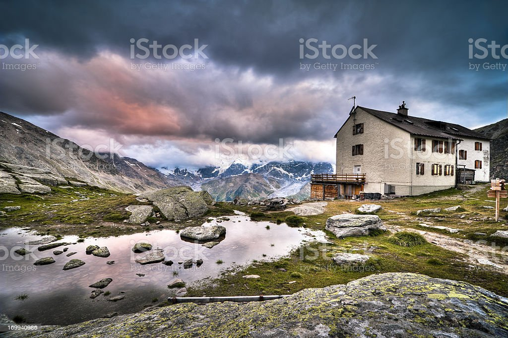 High mountain shelter at sunset stock photo