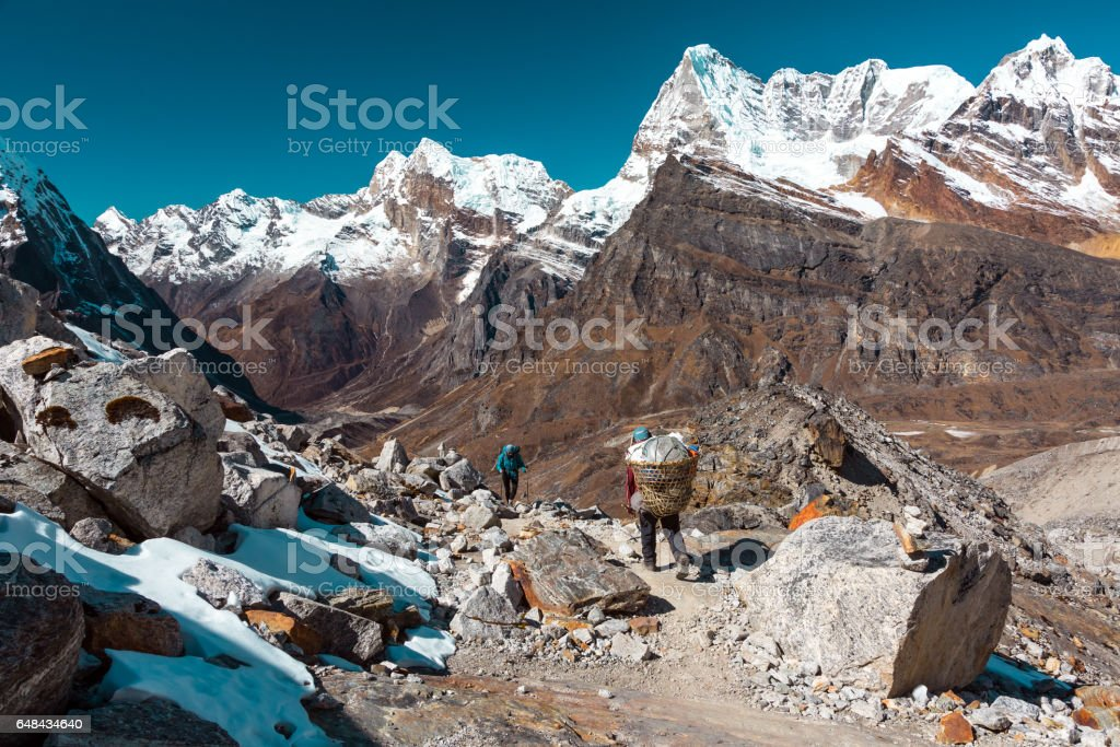 High Mountains Nepalese Porter and European Hiker meeting on Footpath stock photo