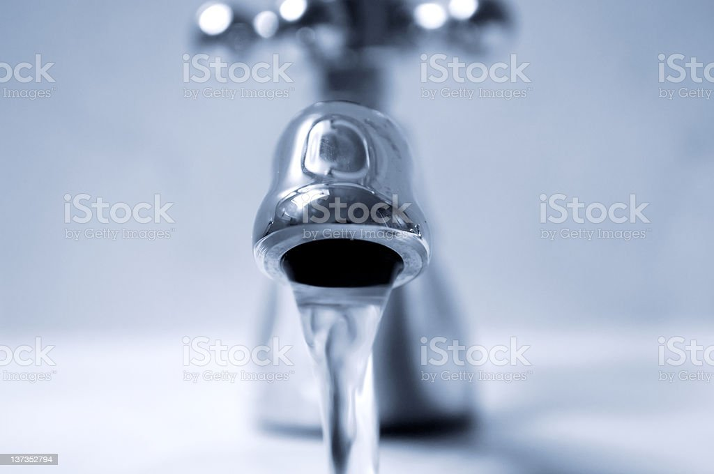 A high res photo of a faucet with running water stock photo
