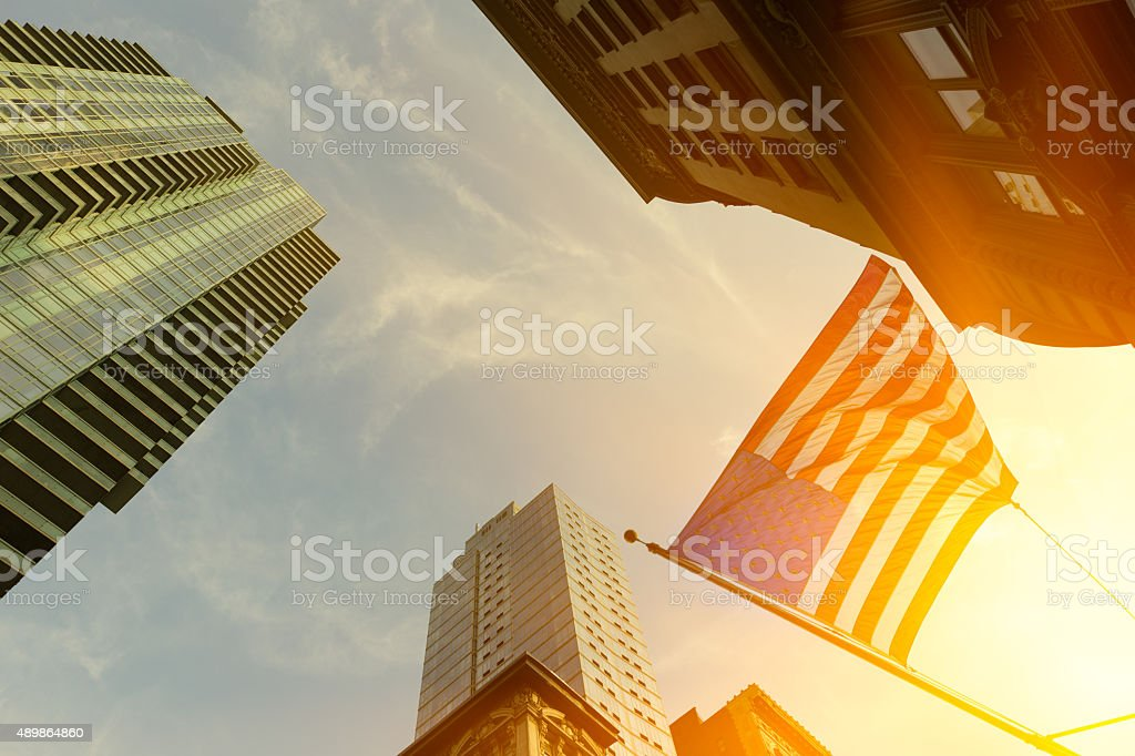 High rise buildings and US flag with red sun behind stock photo