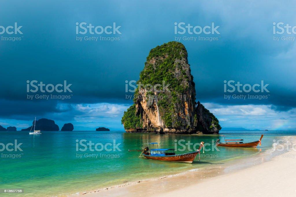 high rock in the sea, rain cloud and Thai boats near the shore stock photo
