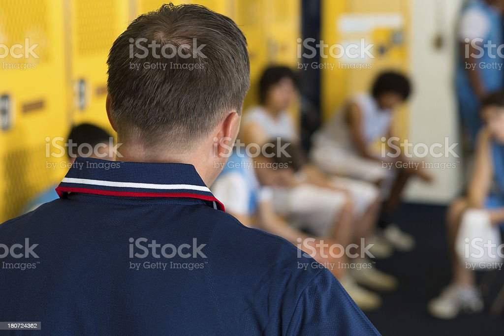 High school athletic director talking to students in locker room stock photo