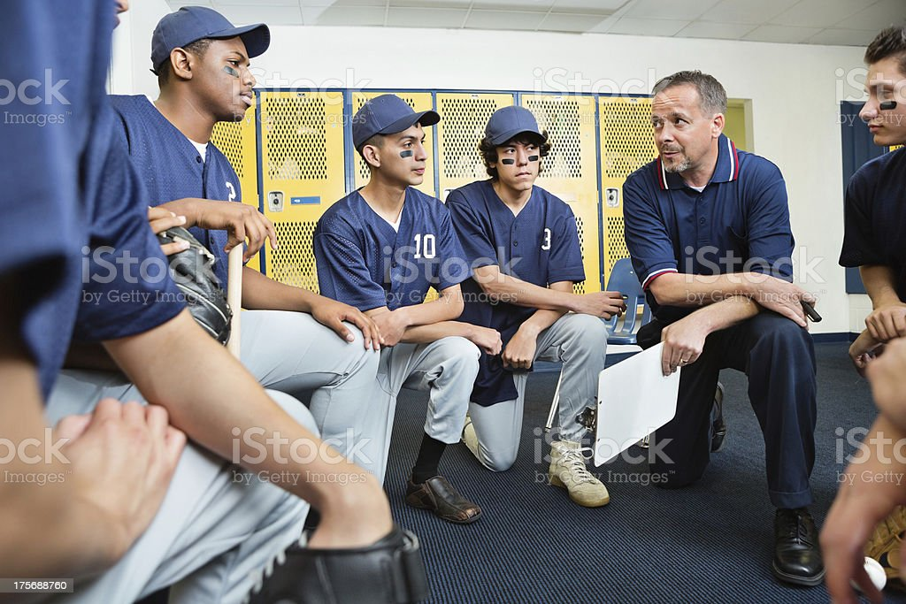 High school baseball coach talking with players in locker room stock photo