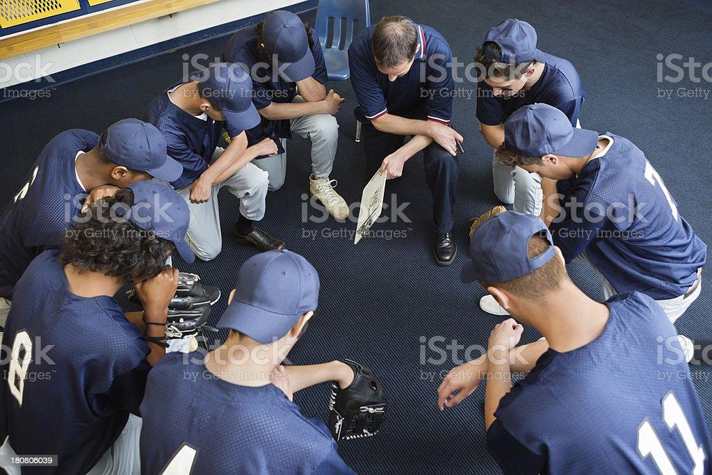 High school baseball players praying together in locker room royalty-free stock photo