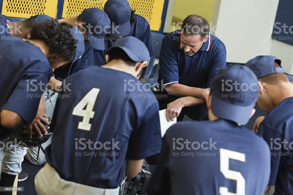 High school baseball team praying together in locker room royalty-free stock photo
