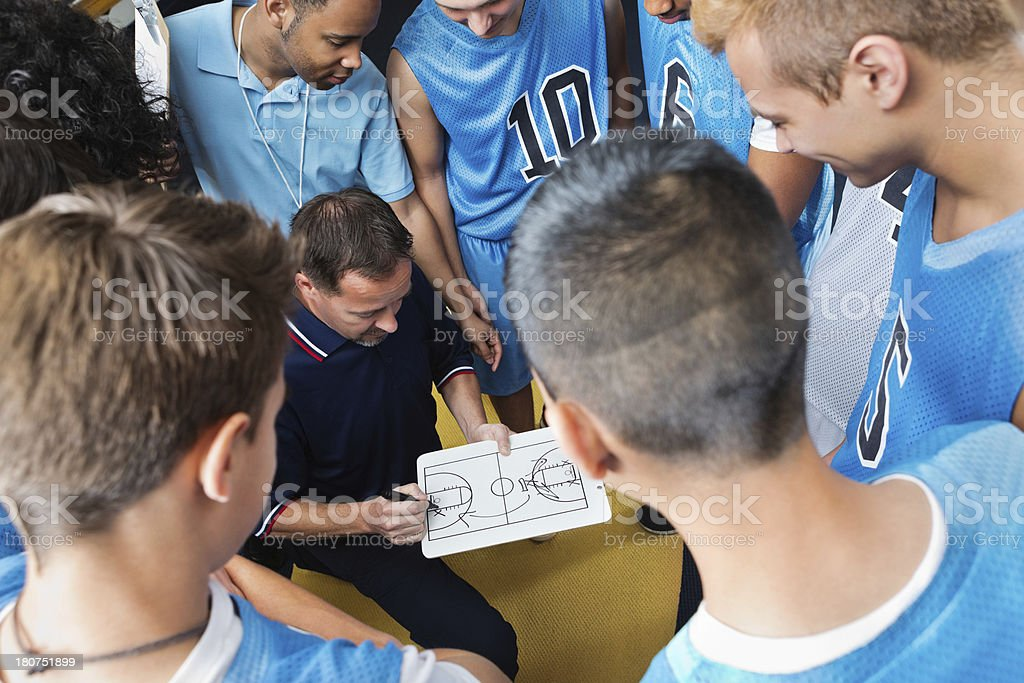 High school basketball coach explaining play to team stock photo