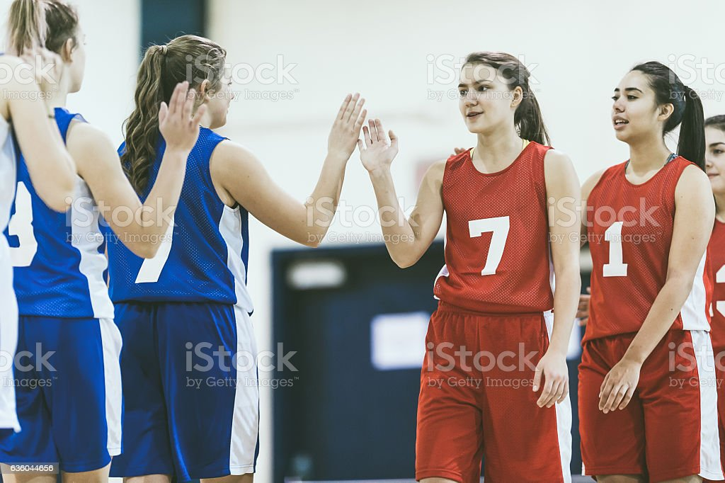 High school basketball oponents high fiving after game stock photo