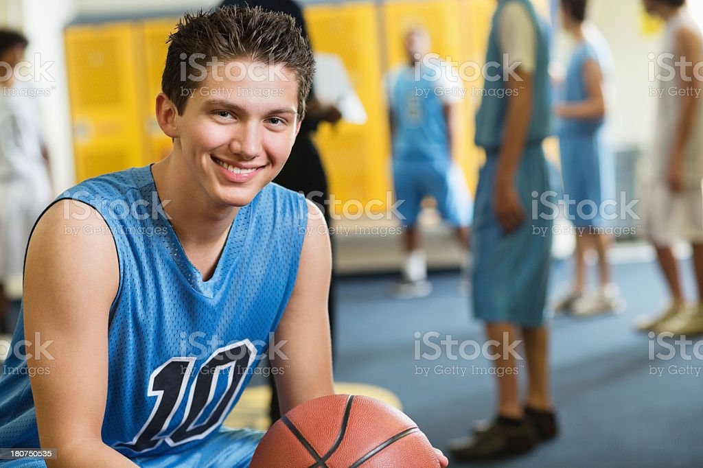 High school basketball player in locker room after winning game stock photo