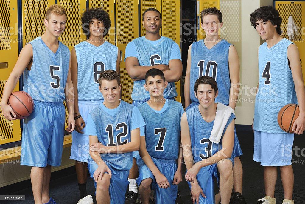 High school basketball team posing in locker room