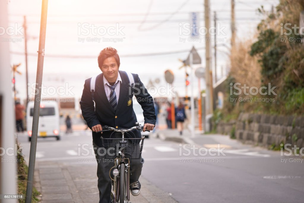 High school boy riding bicycle on slope stock photo