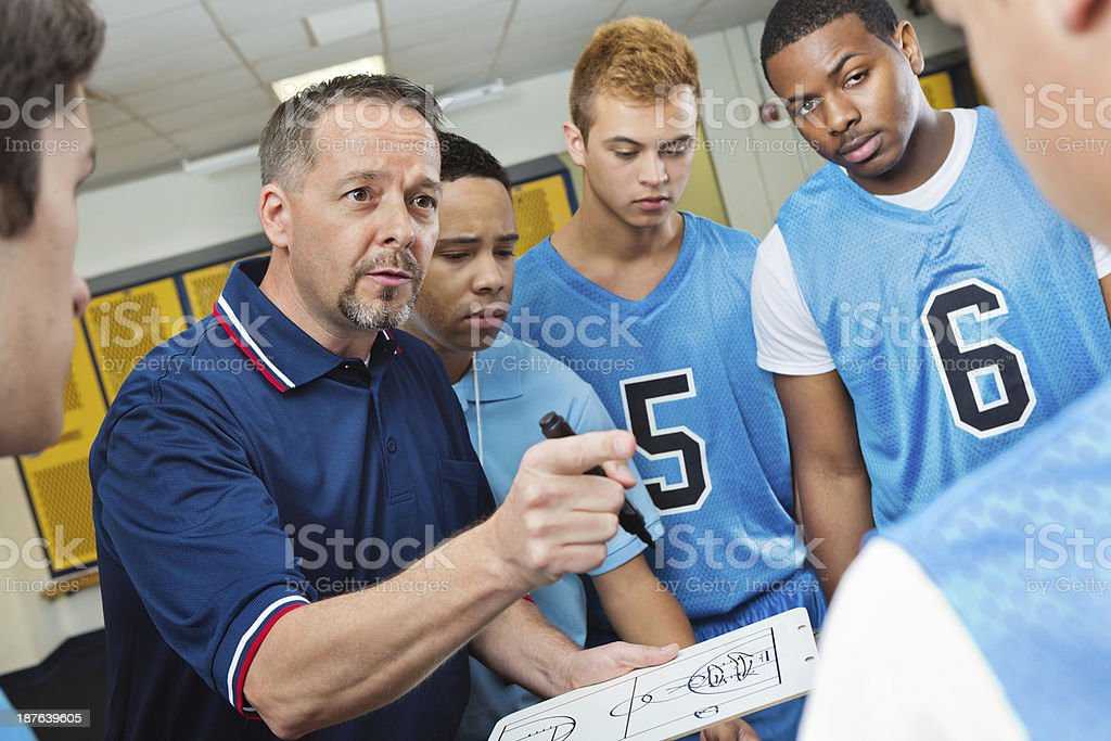 High school coach instructing basketball players in locker room stock photo