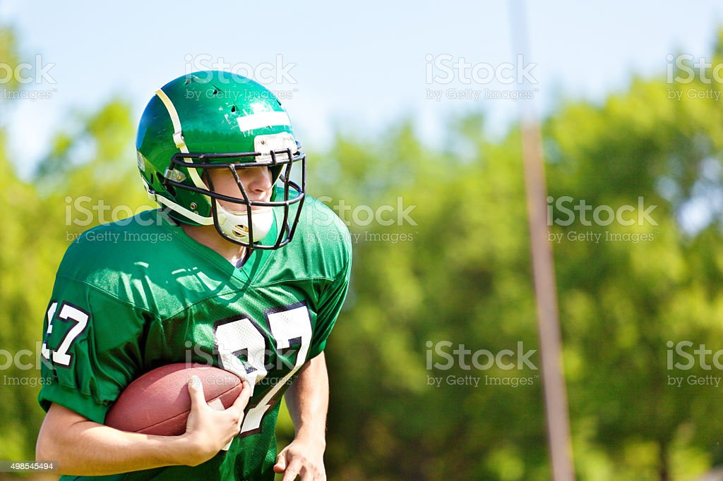 High School College American Football Player Running with Football stock photo