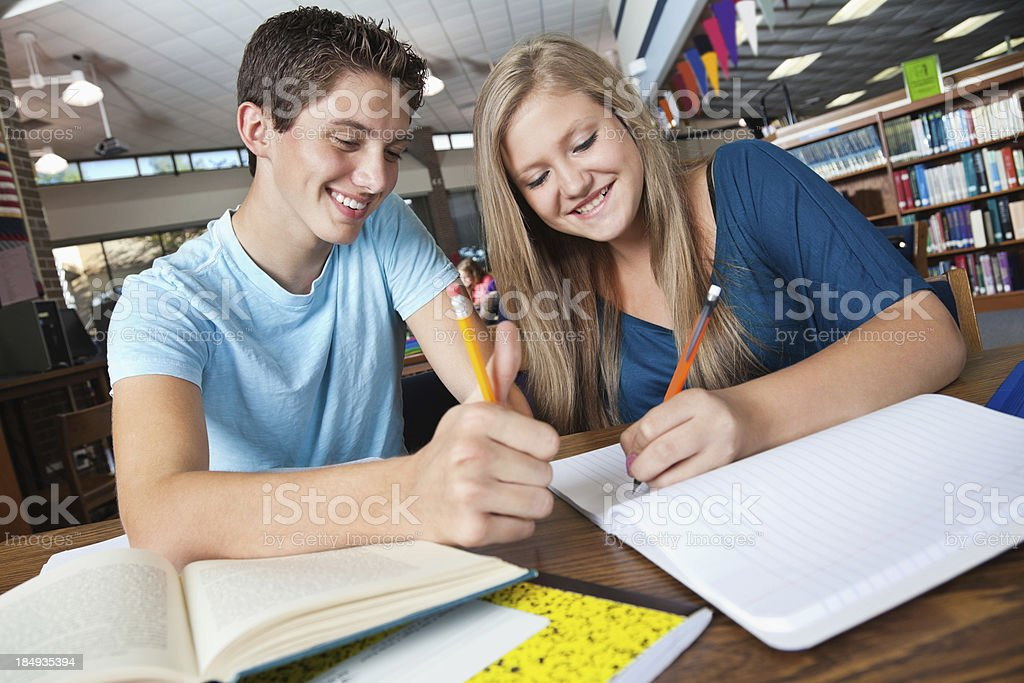 High school friends studying together in the library royalty-free stock photo