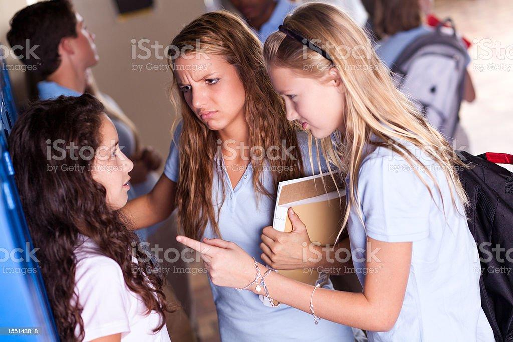 High school girl bullies in the hallway stock photo
