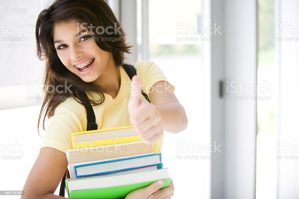 High school girl holding stack of books and giving thumbs up stock photo