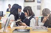 High school girl reading book in classroom