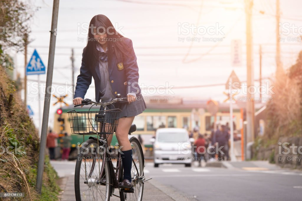 High school girl riding bicycle near station stock photo