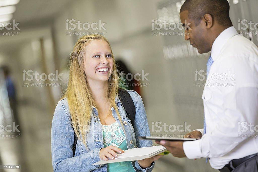 High school girl talking with teacher in hallway near lockers royalty-free stock photo