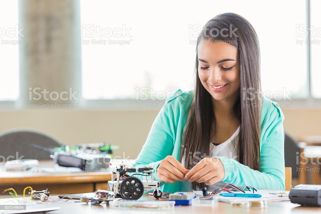 High school girl using kit to build small robot stock photo