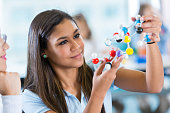 High school girl using molecule models during science class