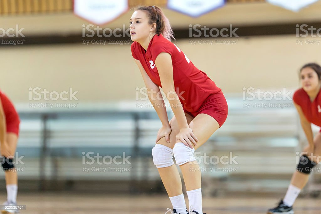 High school girl with hands on knees returning volleyball serve stock photo