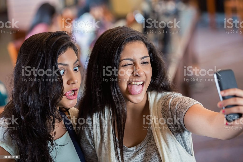 High school girls making silly faces while taking selfie photo stock photo