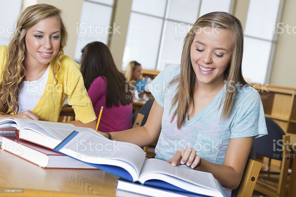 High school girls studying together in library royalty-free stock photo