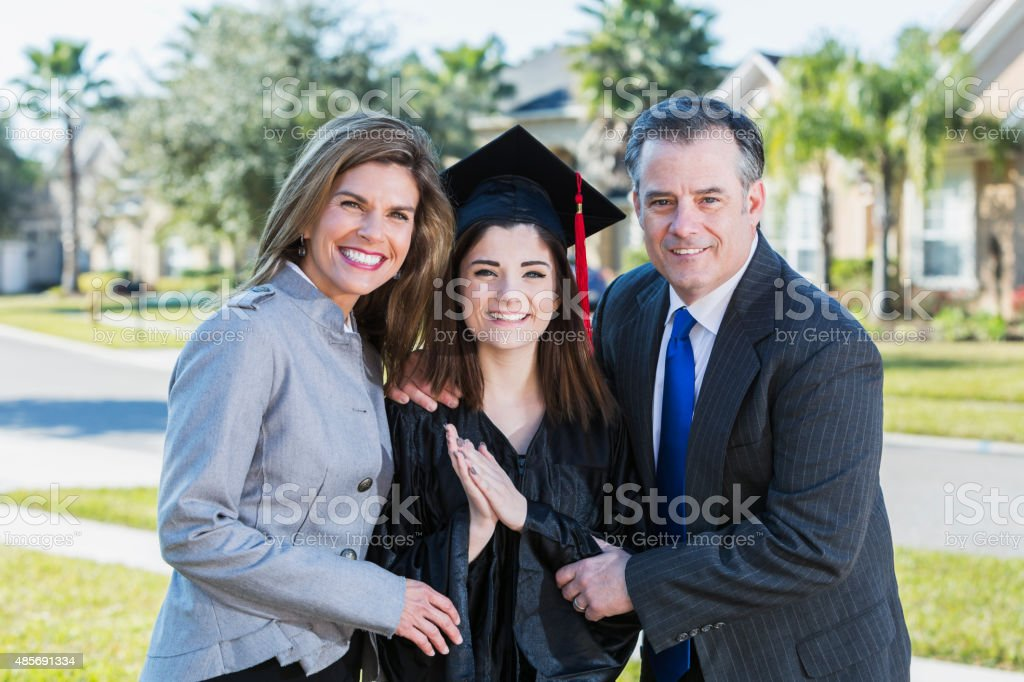 High school graduate posing with her parents stock photo