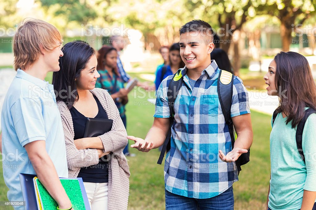 High school or college friends talking after class outdoors stock photo