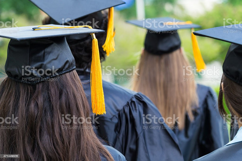 High school or college graduates walking across lawn stock photo
