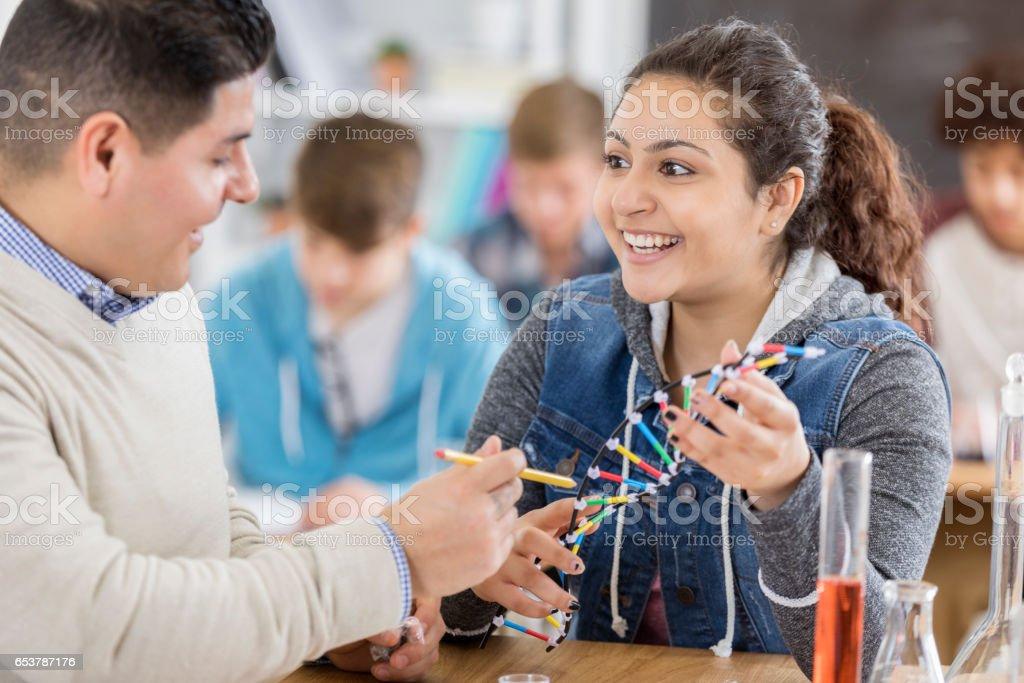 High school science teacher uses DNA helix model in class stock photo