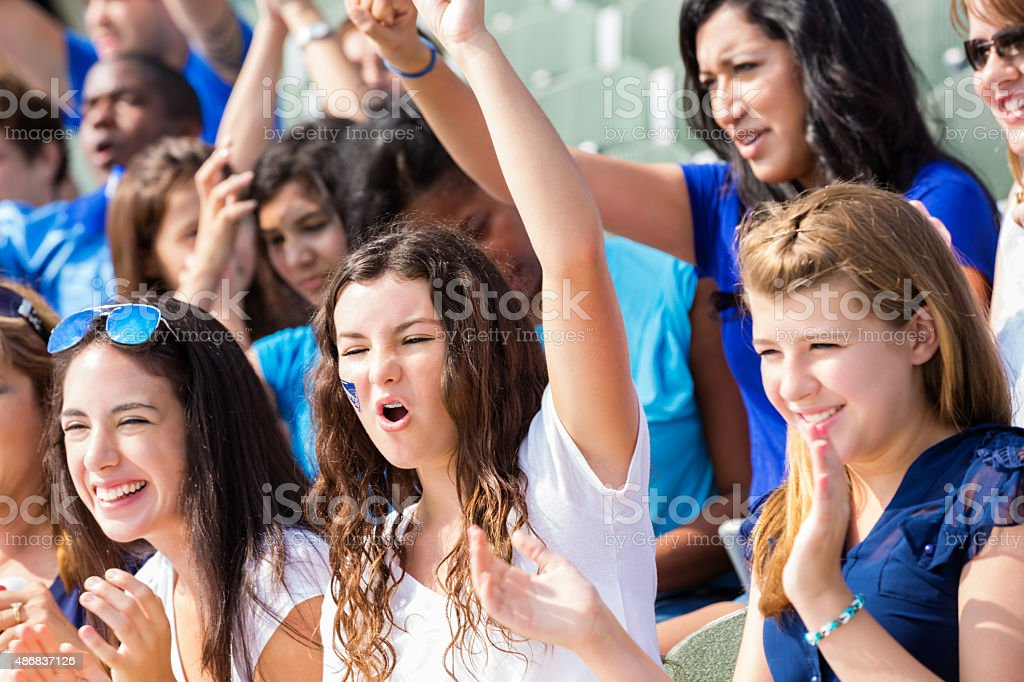 High school sports fans cheering for team in stadium stock photo