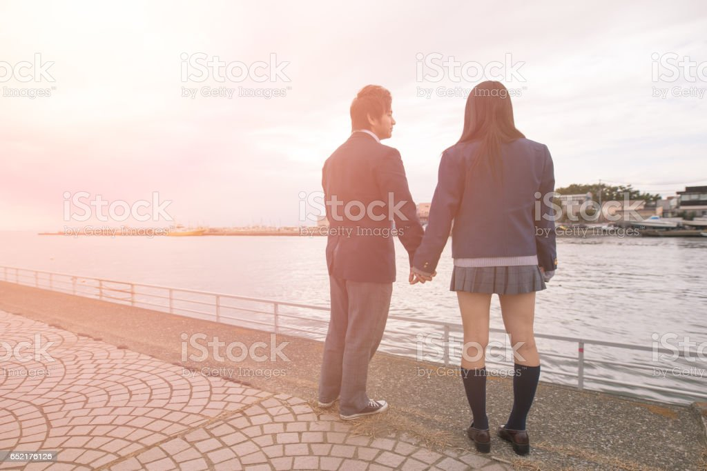 High school student couple looking at sea stock photo