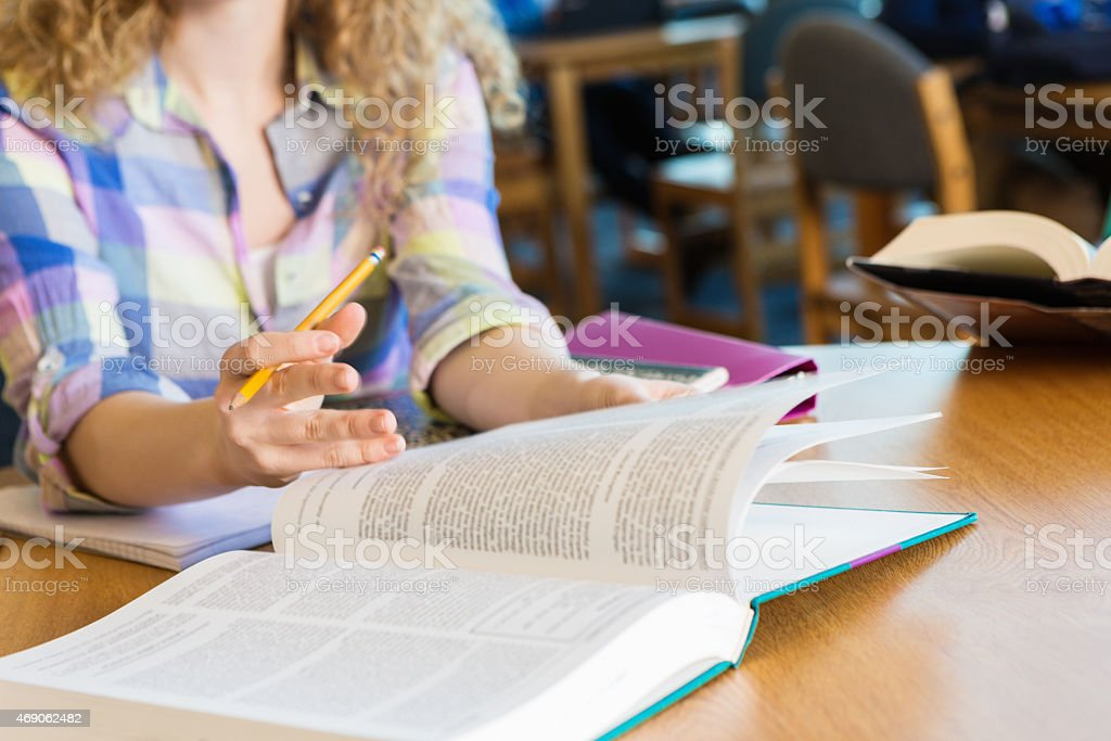 High school student flipping through pages of textbook in library stock photo