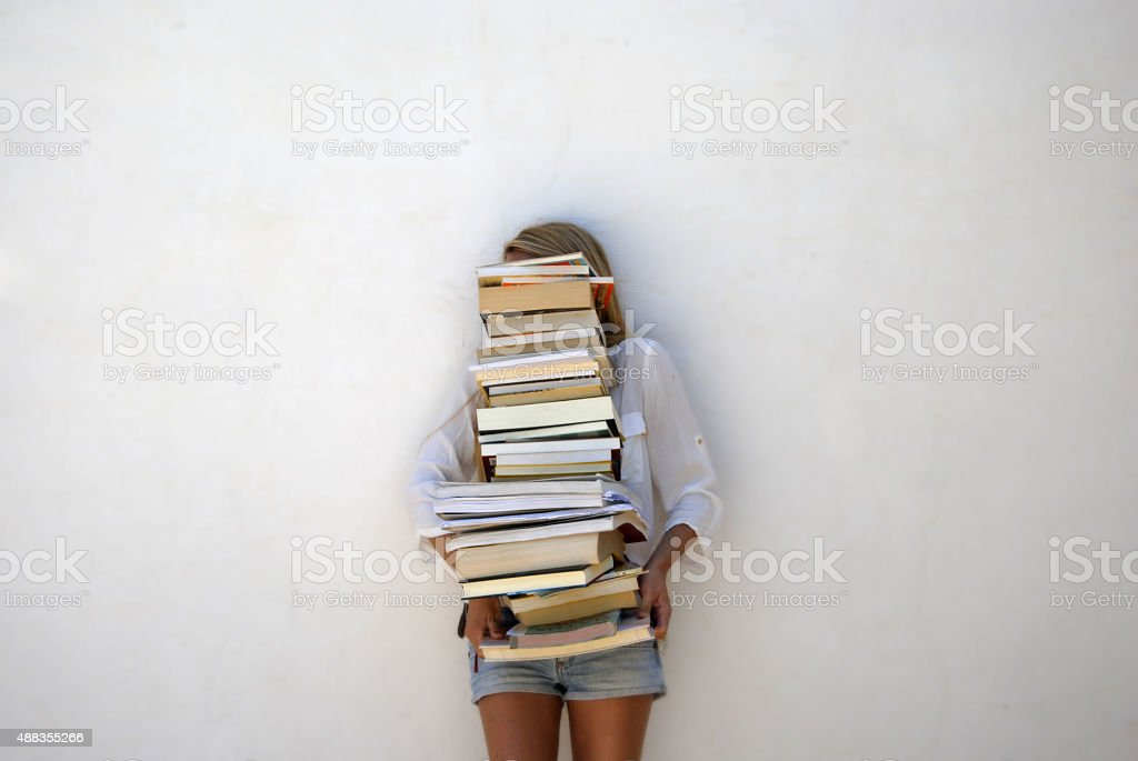 High School Student Holding Lots of Books stock photo
