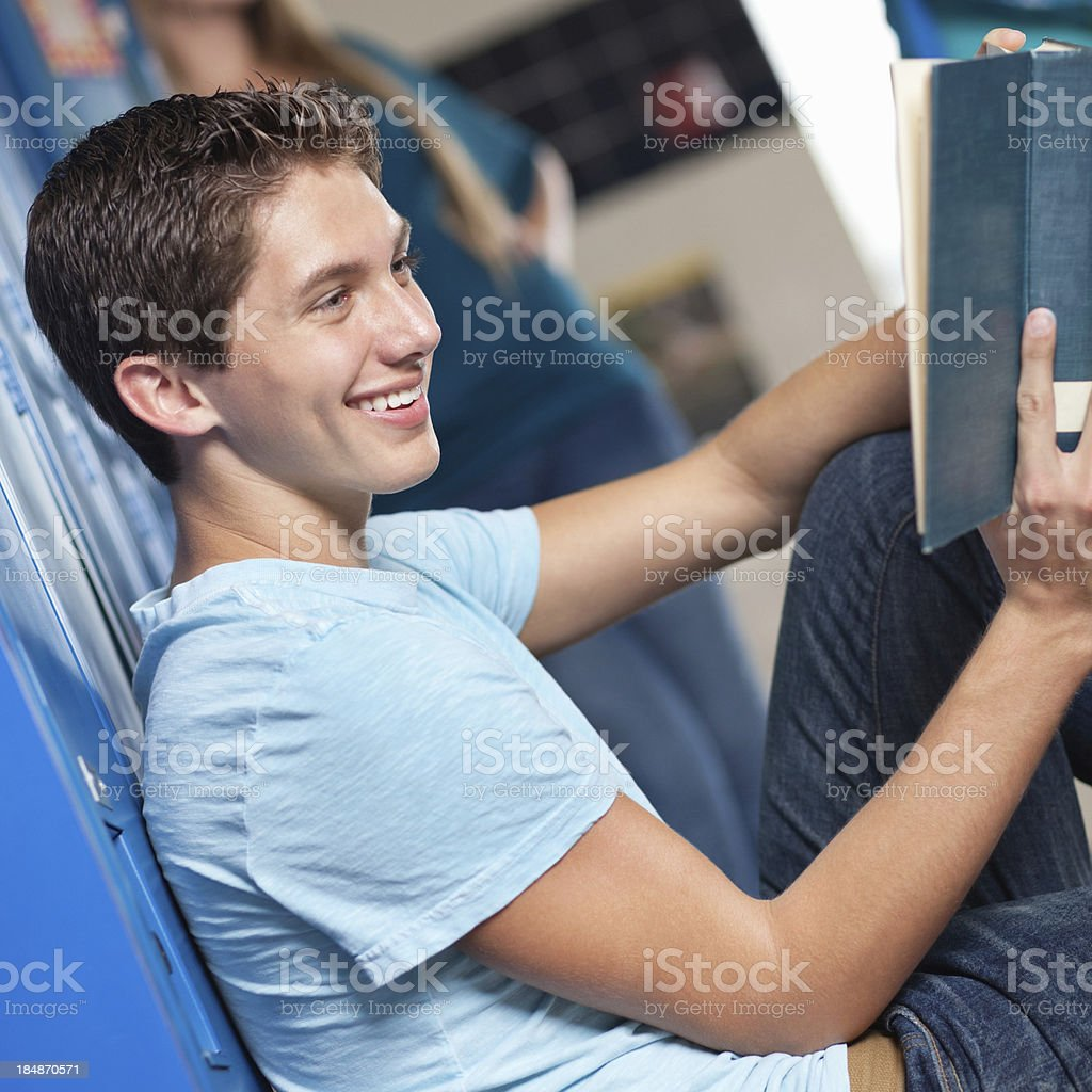 High school student reading at his locker in the hallway royalty-free stock photo