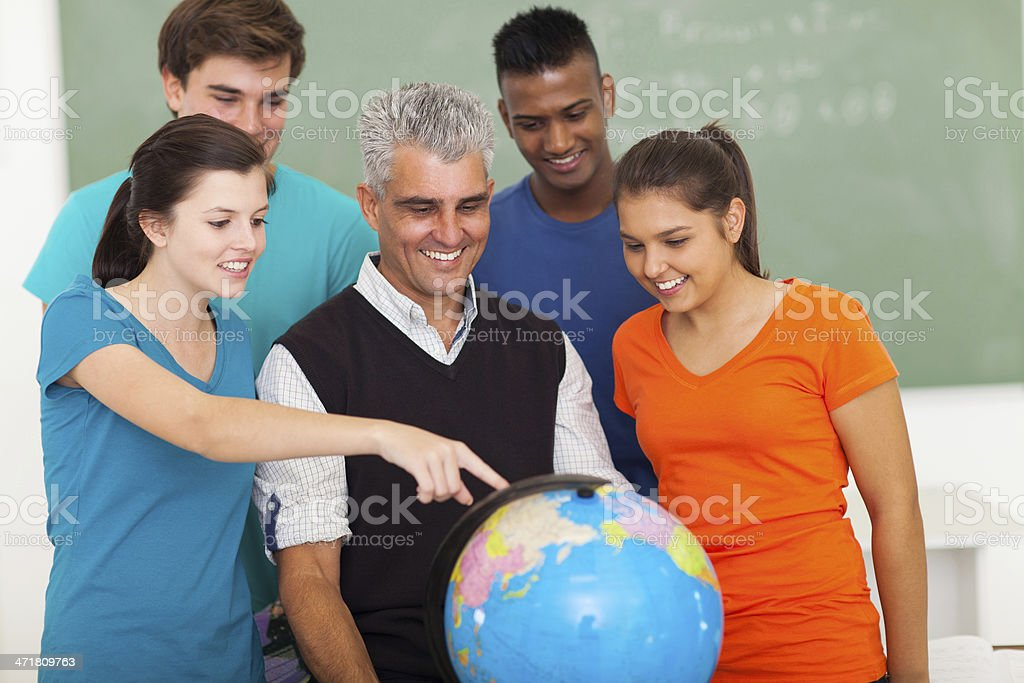 high school students and teacher looking at globe royalty-free stock photo